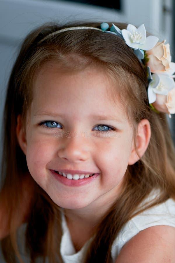 Powabna dziewczyna z długim blondynu włosy, skocznymi niebieskimi oczami i uszczypniętym nosem bezel jest handmade Ono uśmiecha s zdjęcia stock