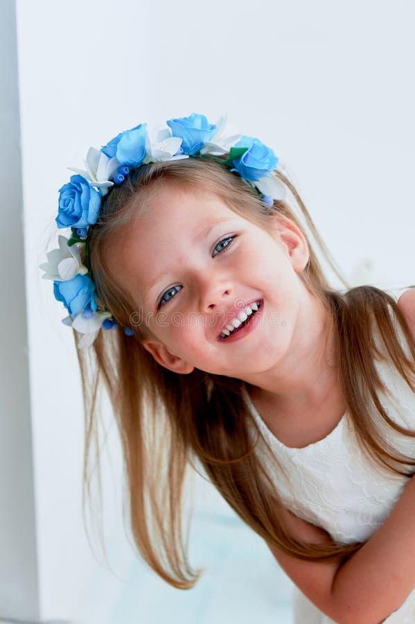Powabna dziewczyna z długim blondynu włosy, skocznymi niebieskimi oczami i uszczypniętym nosem bezel jest handmade Ono uśmiecha s fotografia stock