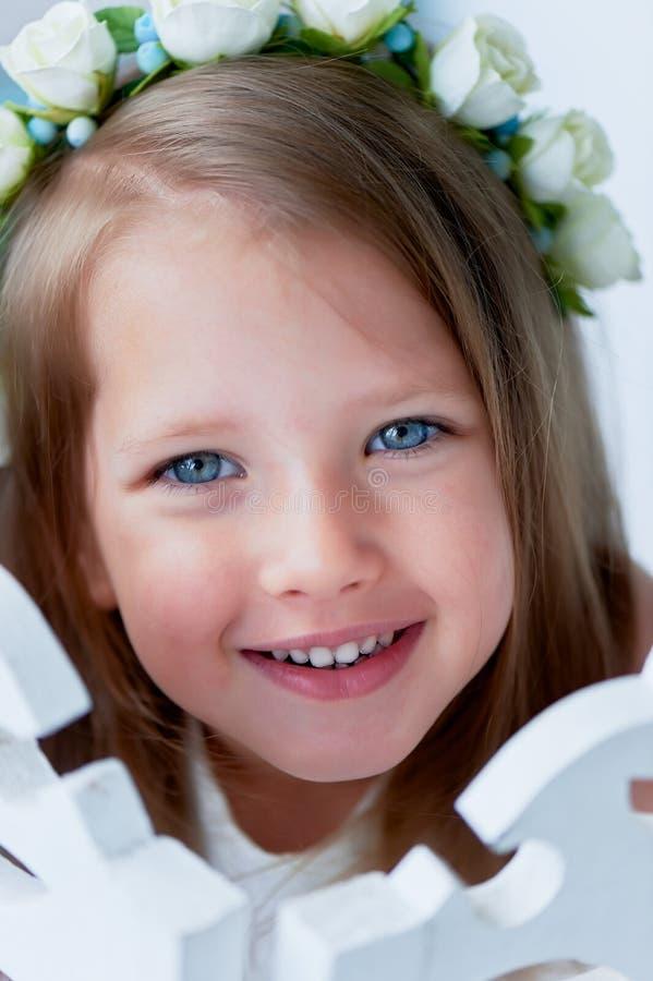 Powabna dziewczyna z długim blondynu włosy, skocznymi niebieskimi oczami i uszczypniętym nosem bezel jest handmade Ono uśmiecha s obrazy royalty free