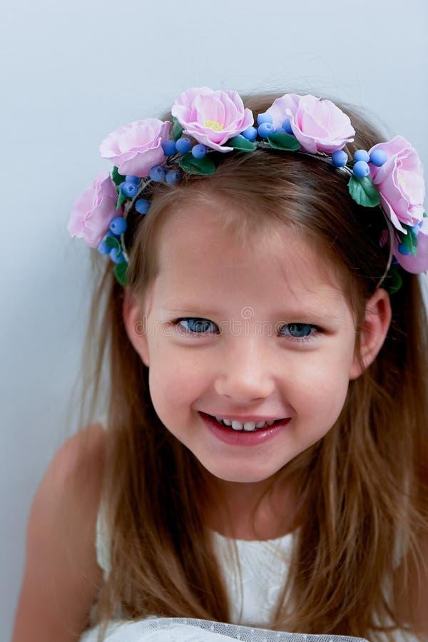 Powabna dziewczyna z długim blondynu włosy, skocznymi niebieskimi oczami i uszczypniętym nosem bezel jest handmade Ono uśmiecha s obraz stock