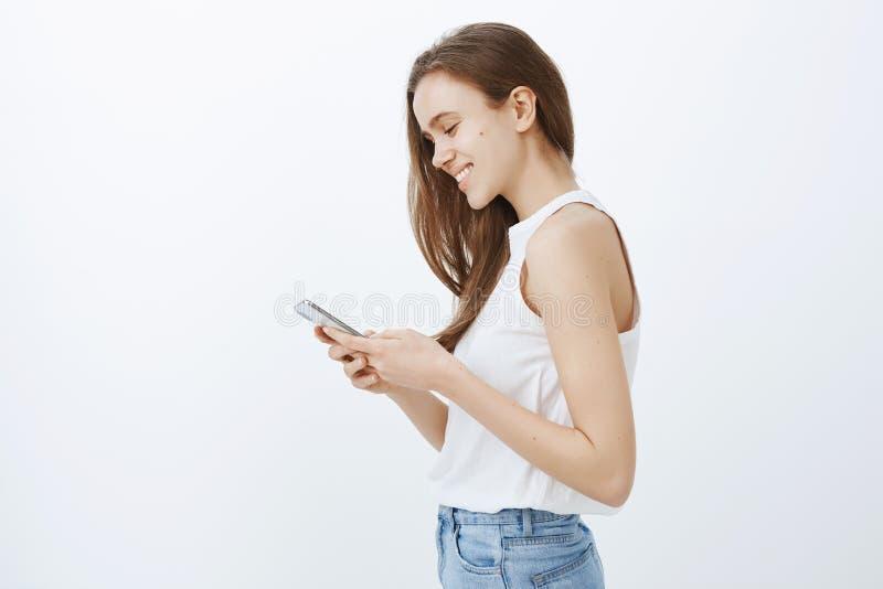 Powabna europejska kobieta w podkoszulek bez rękawów pozyci w profilu z smartphone w rękach, ono uśmiecha się szeroko podczas gdy fotografia stock