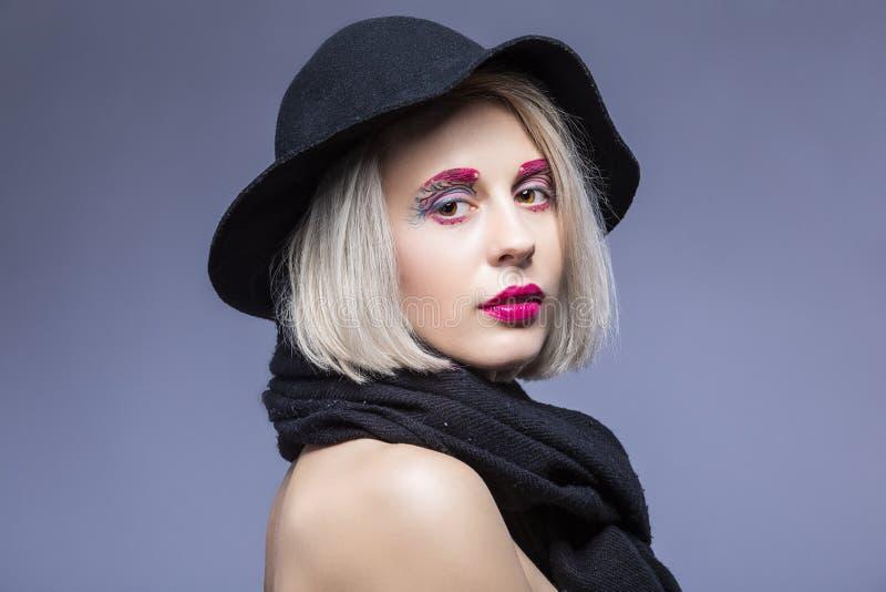 Powabna Kaukaska Blond dziewczyna w czarnym kapeluszu Nad Szarym t?em z Twarzowym makija?em obraz stock