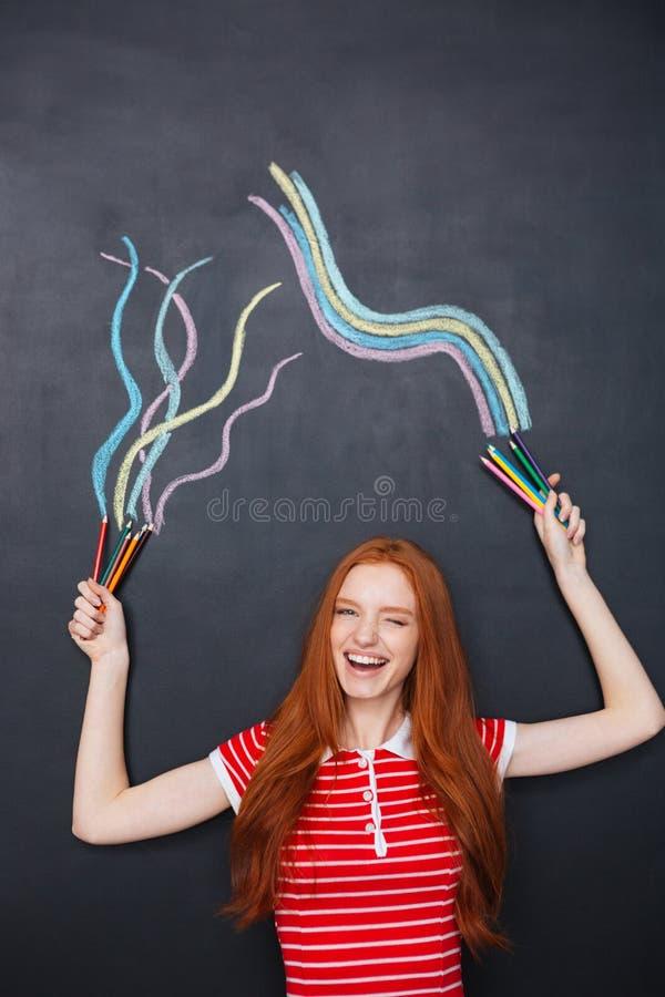 Powabna kobieta śmia się i rysuje na blackboard tle zdjęcie royalty free