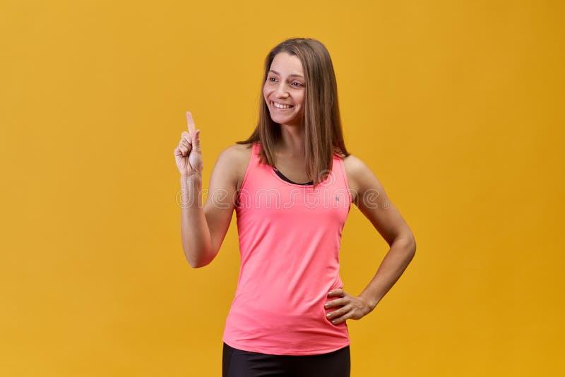 Powabna kobieta z długie włosy i pięknym śnieżnobiałym uśmiechem w menchia sportów koszula na odosobnionym tle zdjęcia stock