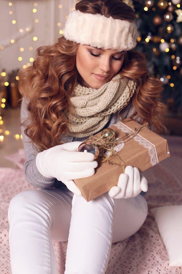 Powabna kobieta z kędzierzawym włosy w ciepłej wygodnej zimy odzieżowym posin zdjęcia stock
