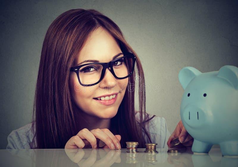 Powabna kobieta z monetami i prosiątko bankiem zdjęcia stock