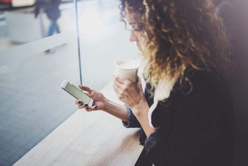 Powabna kobieta z pięknym uśmiechem używać telefon komórkowego podczas odpoczynku w sklep z kawą zamazujący tło obraz royalty free