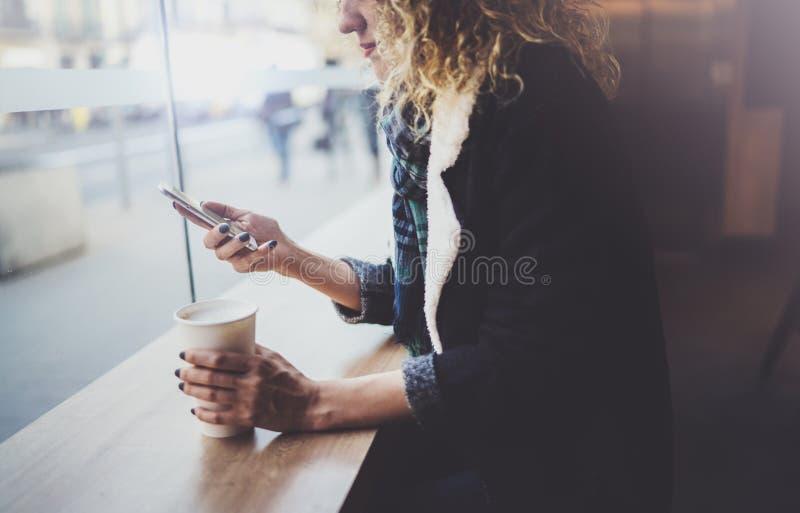Powabna kobieta z pięknym uśmiechem używać telefon komórkowego podczas odpoczynku w sklep z kawą zamazujący tło fotografia stock