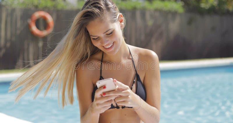 Powabna kobieta z telefonem w basenie obrazy stock