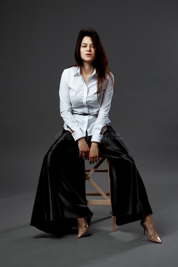 Powabna młoda kobieta ubierająca w białej koszula z czarnym paskiem i szerokimi czarnymi spodniami siedzi na drewnianej stolec na zdjęcie royalty free