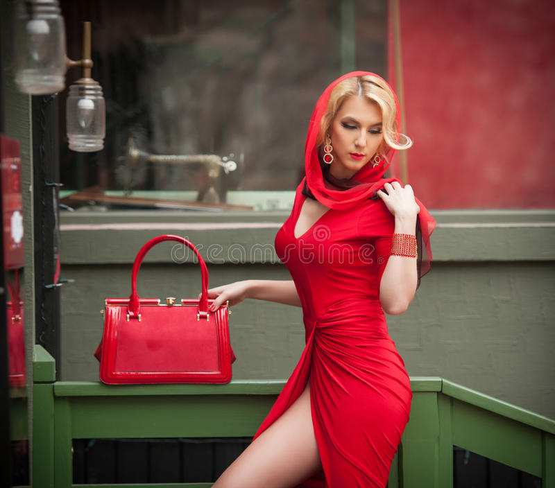 Powabna młoda blondynka z czerwieni suknią, kierowniczym szalikiem i torbą, Zmysłowa wspaniała młoda kobieta w czerwonym stroju z zdjęcie royalty free
