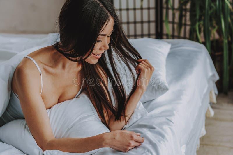 Powabna młoda dziewczyna ma odpoczynek w wygodnej sypialni w domu obraz stock
