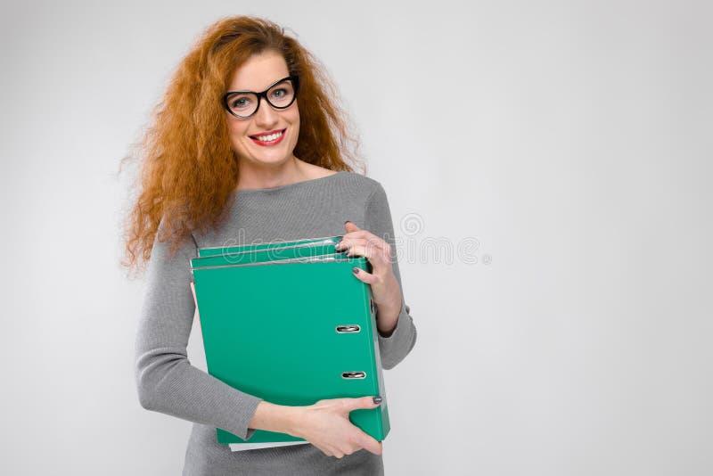 Powabna młoda dziewczyna z czerwonym włosy Młoda dziewczyna w szarym pulowerze tła dziewczyny szarość potomstwa Młoda dziewczyna  zdjęcie stock