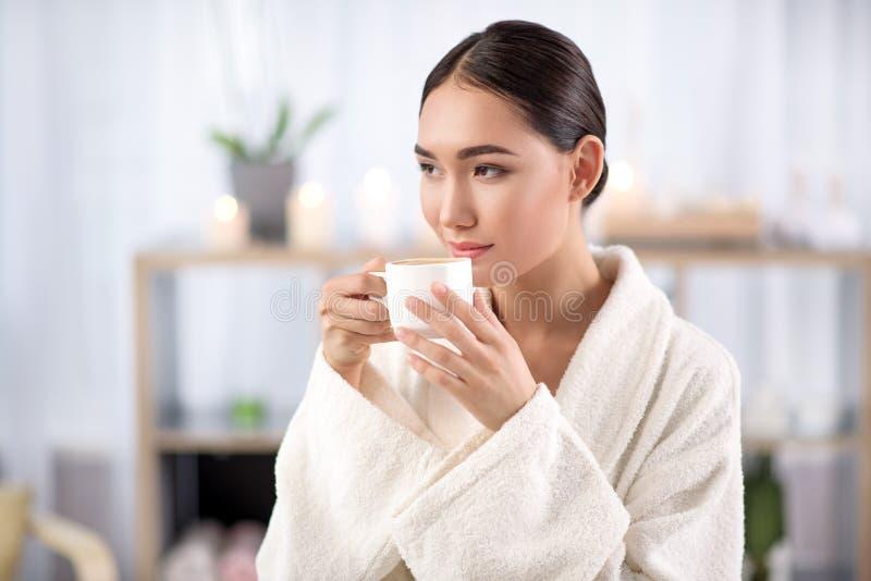 Powabna młoda kobieta cieszy się napój w wellness centrum fotografia stock