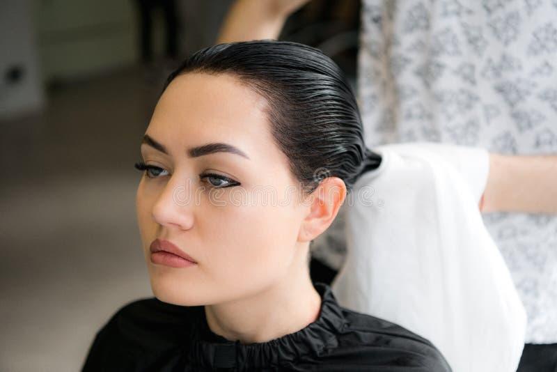 Powabna młoda kobieta ono uśmiecha się szczęśliwie podczas gdy fachowy męski hairstylist przygotowywa jej włosy dla ostrzyżenia s obrazy royalty free