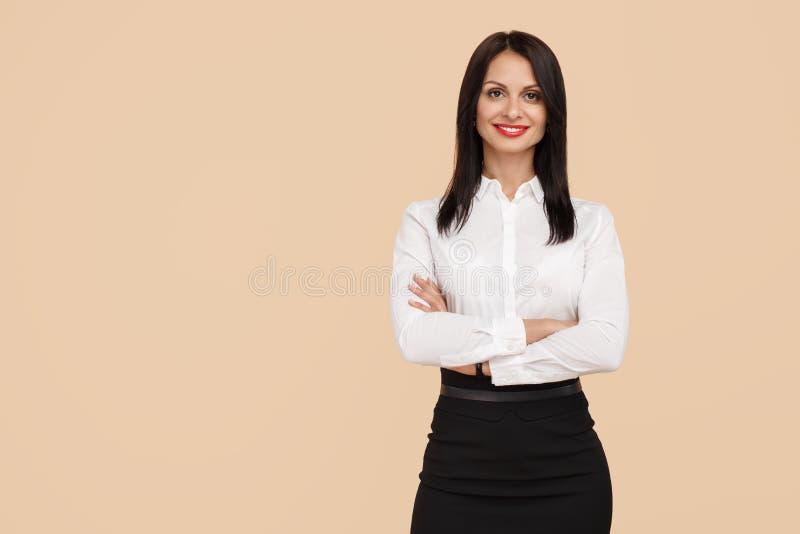 Powabna młoda nowożytna biznesowa kobieta stoi nad beżowym tłem Sukces i zwycięzcy pojęcie zdjęcia royalty free