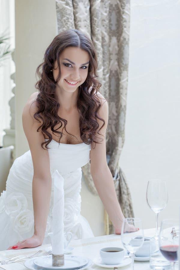 Powabna młoda panna młoda pozuje blisko bankieta stołu zdjęcia royalty free