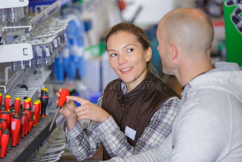 Powabna młoda sprzedawczyni w fartuchu z narzędziami w supermarkecie obraz stock