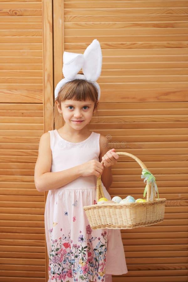 Powabna mała dziewczynka w sukni z białymi królików ucho na jej głowie trzyma kosz z farbującymi jajkami na obrazy stock