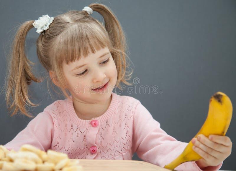 Powabna mała dziewczynka trzyma dojrzałego banana zdjęcie royalty free