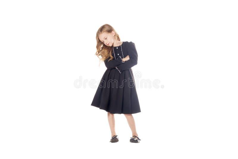 Powabna mała dziewczynka w czarnej sukni z jego rękami krzyżował na jego klatce piersiowej Odizolowywającej na białym tle fotografia royalty free