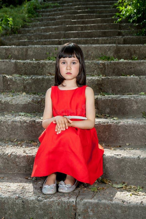 Powabna mała dziewczynka w czerwonej sukni obraz stock