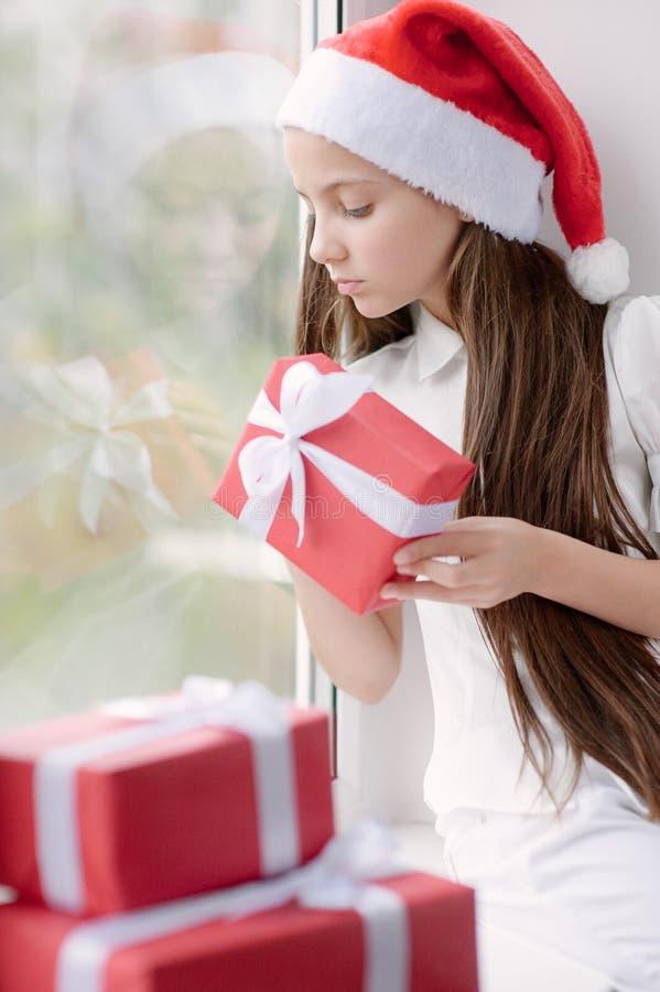 Powabna mała dziewczynka w Santa kapeluszowym obsiadaniu nadokiennym mieniem obrazy royalty free