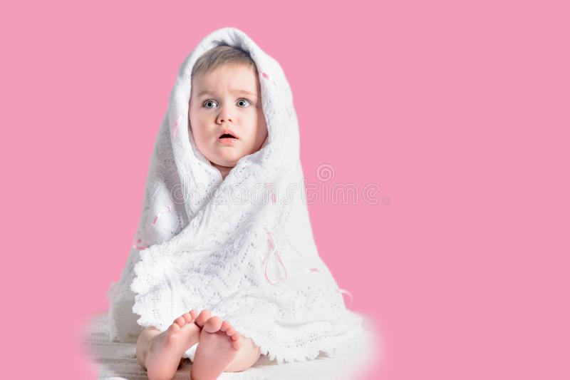 Powabna mała dziewczynka zawijająca w białym szalika obsiadaniu na różowym tle zdjęcia royalty free