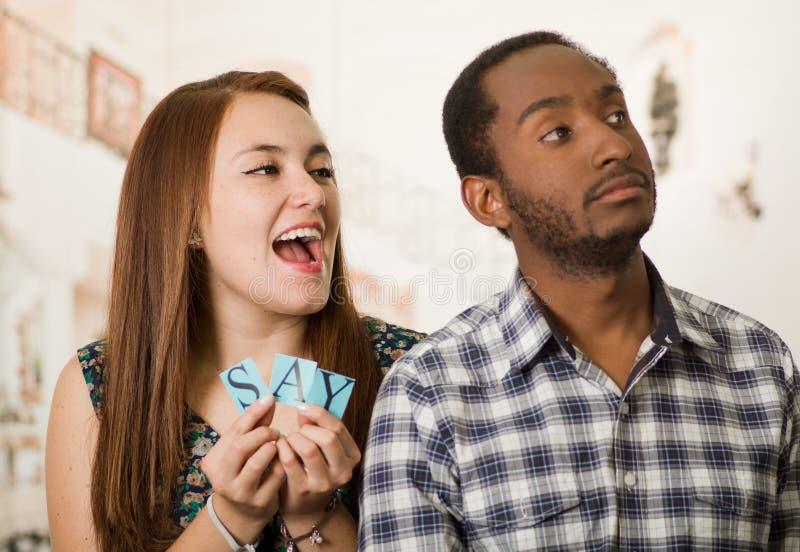Powabna międzyrasowa para trzyma up małych listy literuje powiedzenie podczas gdy oddziałający wzajemnie szczęśliwie, rozmyty stu zdjęcia royalty free