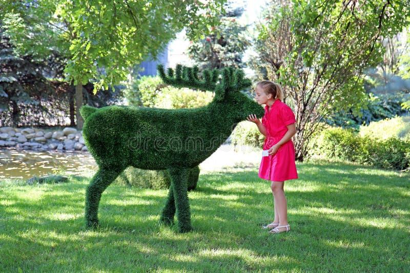 Powabna nastoletnia dziewczyna w różowej sukni blisko krzak rzeźby łoś amerykański obraz stock