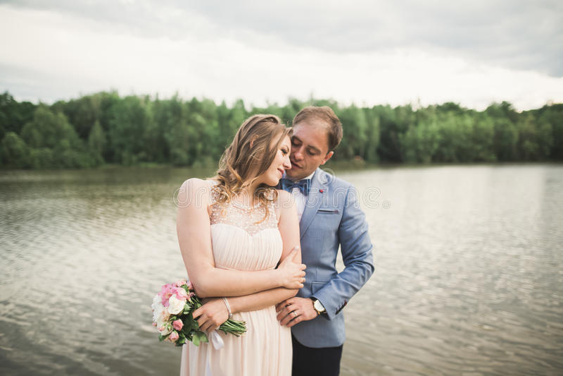 Powabna panna młoda, elegancki fornal na krajobrazach góry i zmierzch przy jeziorem, wspaniały para ślub zdjęcie stock