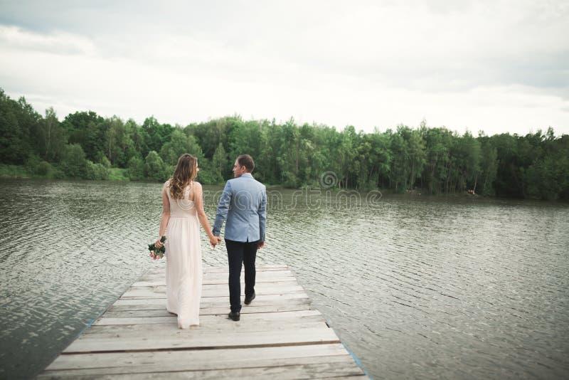 Powabna panna młoda, elegancki fornal na krajobrazach góry i zmierzch przy jeziorem, wspaniały para ślub zdjęcia stock