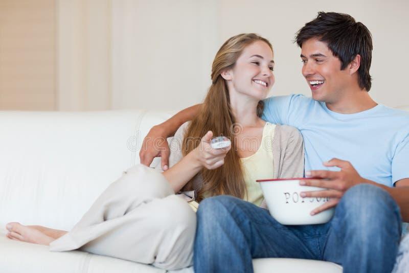 Powabna pary dopatrywania telewizja podczas gdy jedzący popkorn zdjęcia royalty free