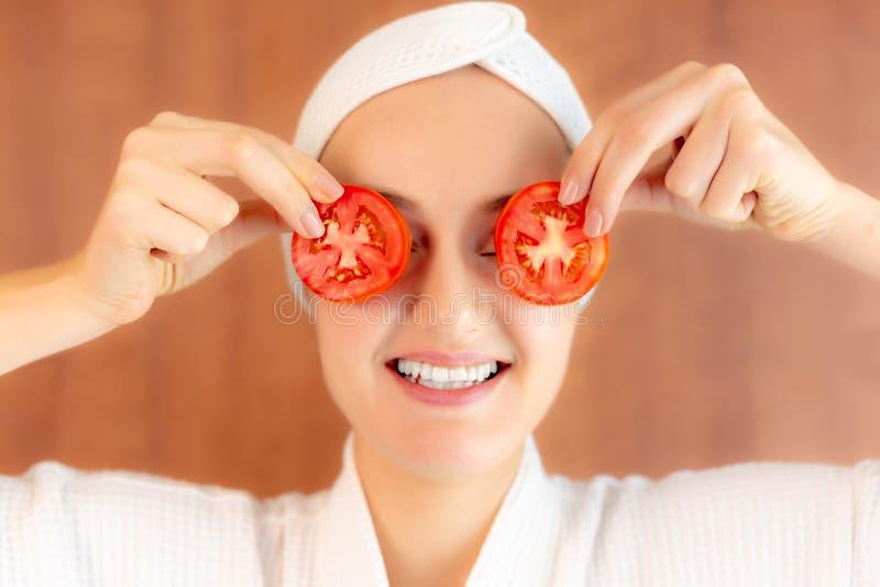 Powabna piękna młoda kobieta używa kawałek pomidor pokrajać zakończenie przy jej domem ona oczy z smiley twarzą Atrakcyjny Pi?kny zdjęcia royalty free