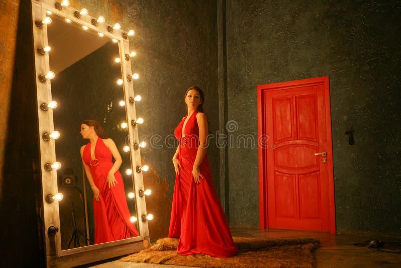 Powabna pi?kna dziewczyna w czerwie? wiecz?r d?ugiej luksusowej sukni na futerkowym dywaniku blisko ogromnego lustra w ramie z ?a fotografia stock