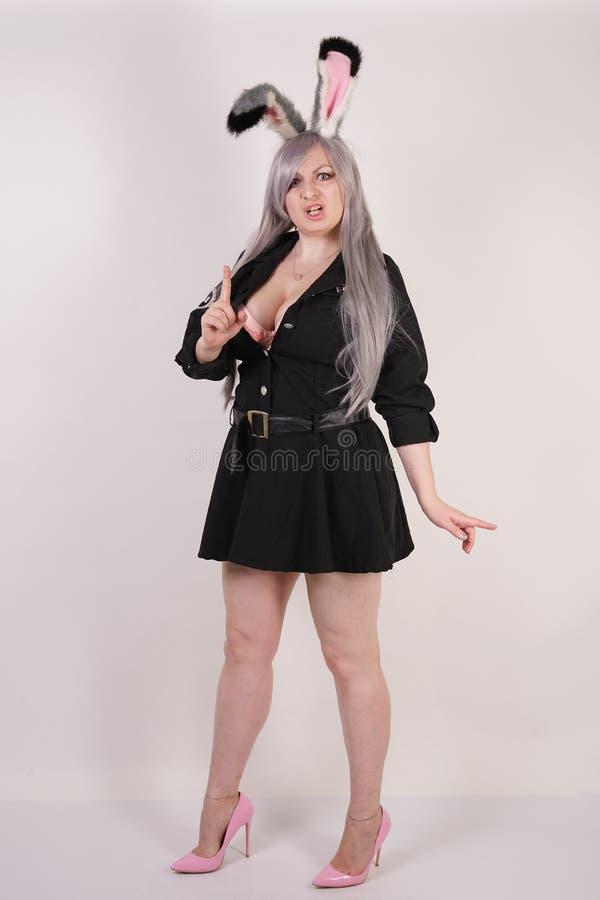 Powabna pyzata dziewczyna w milicyjnym kostiumu z cosplay królików ucho bardzo emocjonalnymi i gniewnymi na białym tle obrazy royalty free