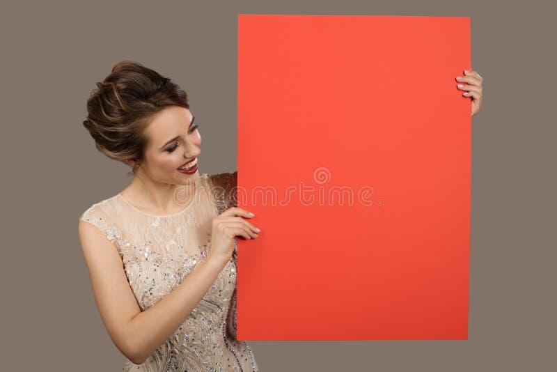 Powabna szcz??liwa kobieta trzyma du?ego czerwie? papieru pustego puste miejsce obraz royalty free