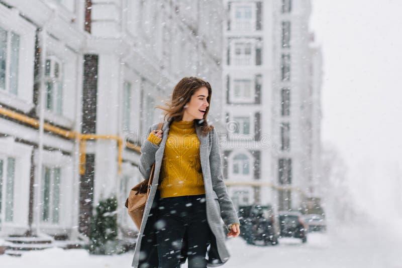 Powabna uśmiechnięta młoda kobieta w żakiecie z plecaka odprowadzeniem w opad śniegu w Europa centrum miasta wyrazi? positivity fotografia stock