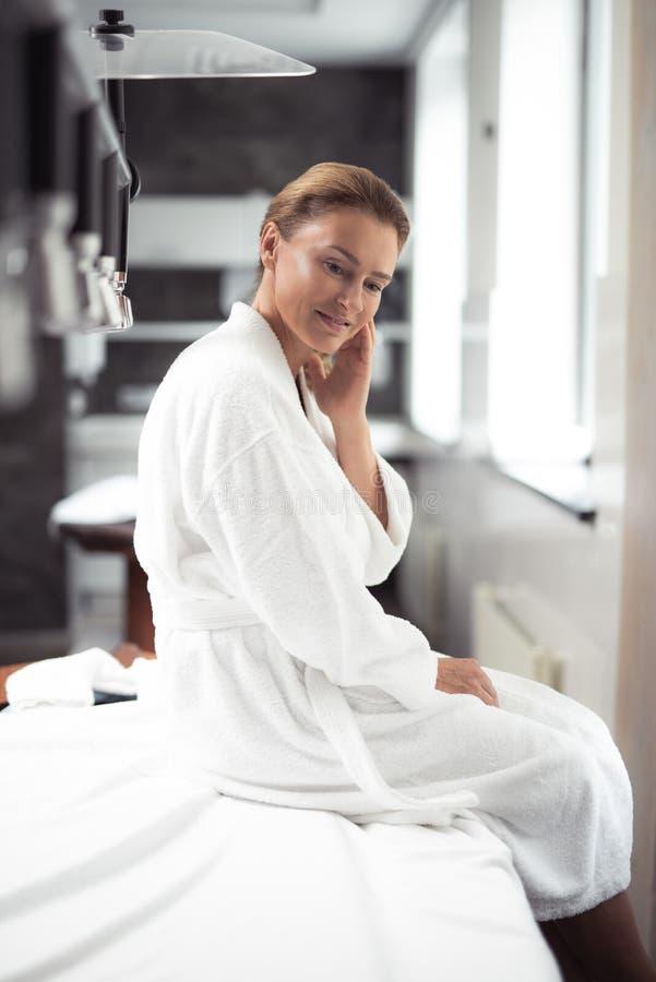 Powabna w średnim wieku kobieta w bathrobe obsiadaniu na masażu stole przy zdroju salonem fotografia royalty free