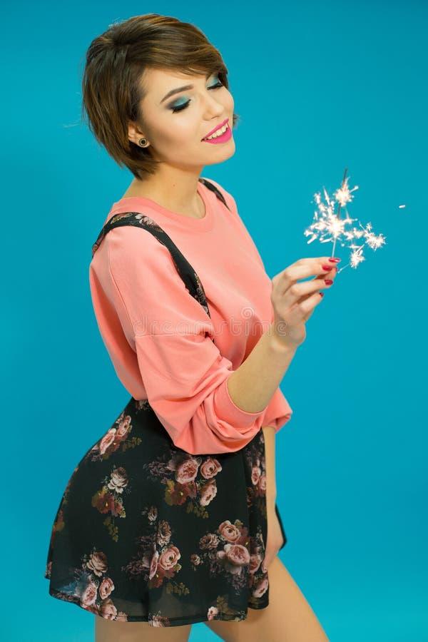 Powabne kobiety jest ubranym różową bluzkę z zimno ogieniem w jej ręce fotografia royalty free