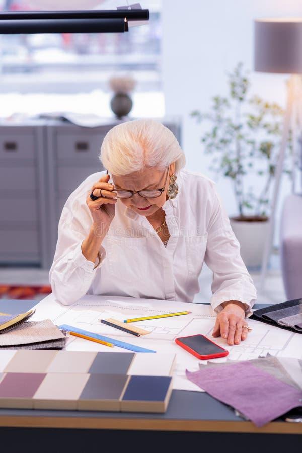 Powabnego starzenia się wiodący projektant concentratedly robi rysunkowi w biurze obrazy stock