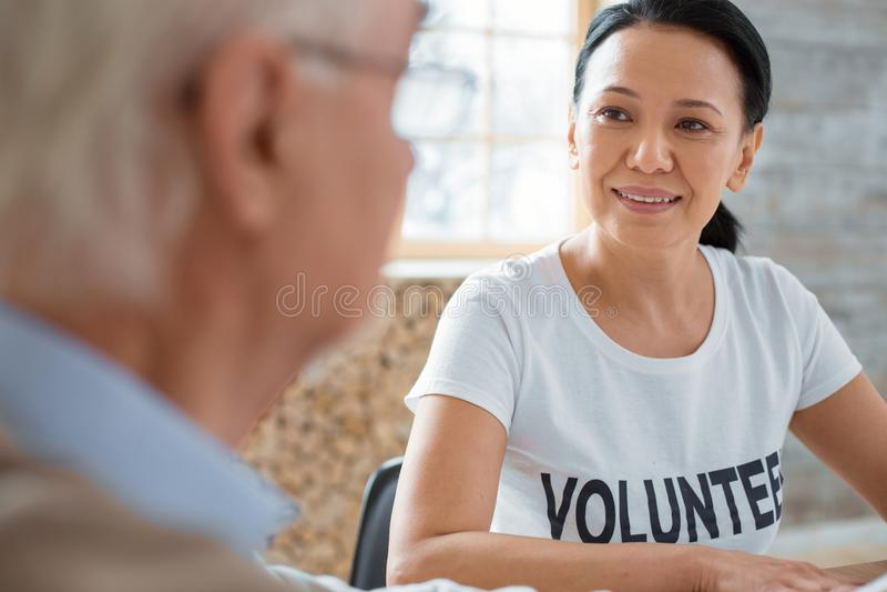 Powabnego wolontariusza i starszego mężczyzna opowiadać fotografia royalty free
