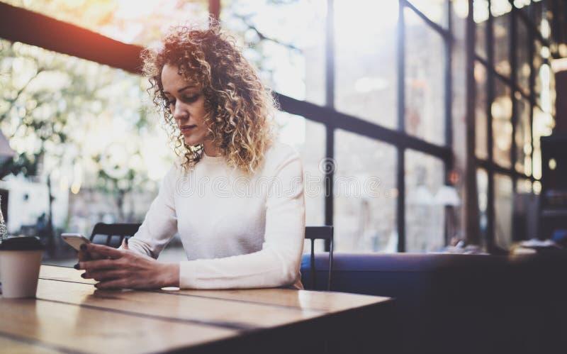 Powabnej pięknej młodej kobiety czytelniczy e-mail na telefonie komórkowym podczas spoczynkowego czasu w sklep z kawą Bokeh i rac obrazy stock