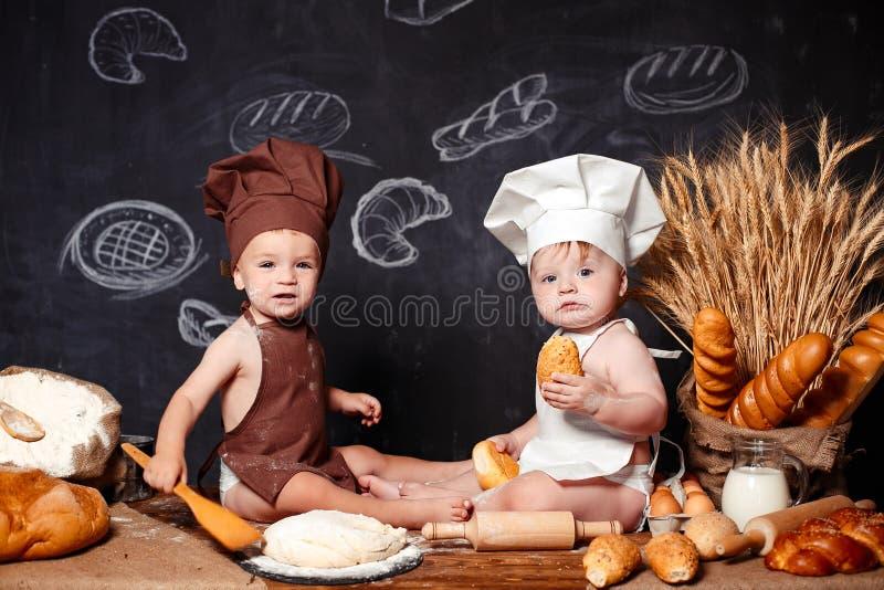 Powabni mali berbecie w fartuchach na stole z chlebem zdjęcia stock