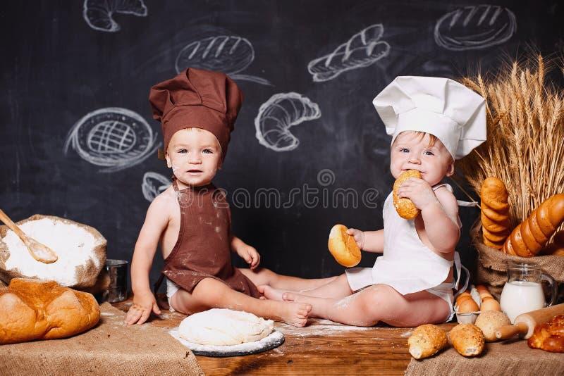 Powabni mali berbecie w fartuchach na stole z chlebem fotografia royalty free