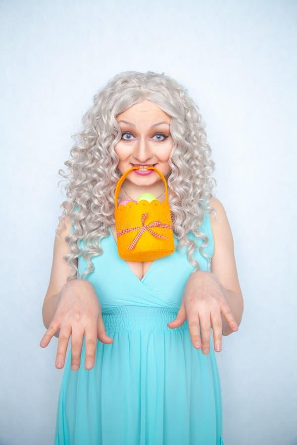 Powabni uśmiechnięci blondynka nastolatka stojaki w błękitnej sukni z pomarańczowym koszem z malującymi jajkami dla Wielkanocnego zdjęcie royalty free