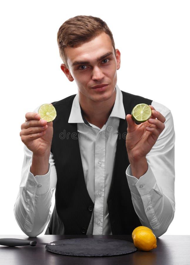 Powabny barman przy prętowym kontuarem trzyma wapno, żółte jaskrawe cytryny na białym tle zdjęcia stock