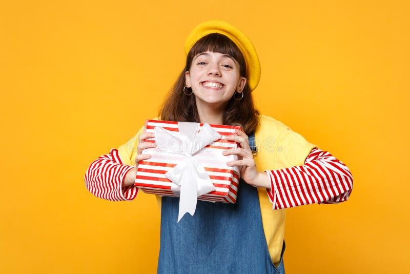 Powabny dziewczyna nastolatek trzyma czerwień w francuskim berecie, drelichowi sundress paskował teraźniejszego pudełko z prezent obraz stock