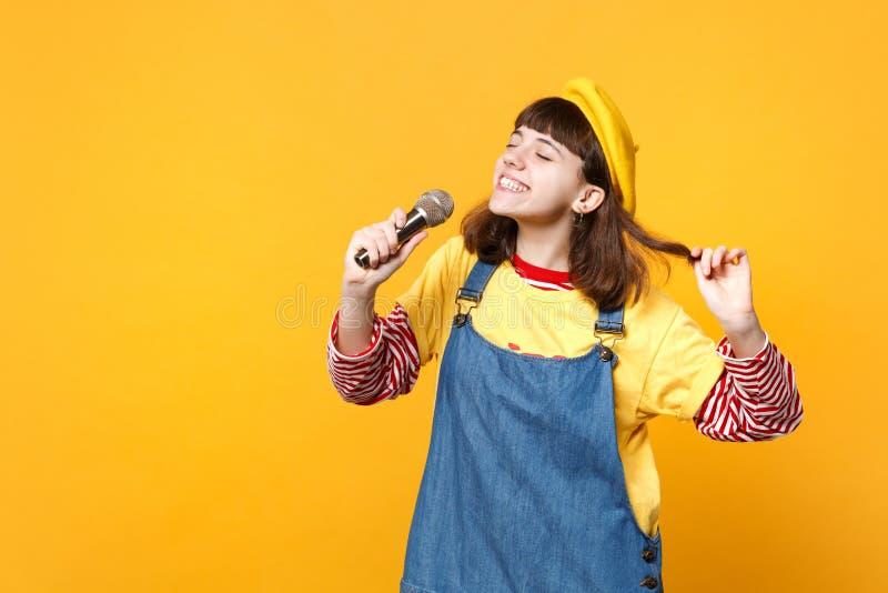 Powabny dziewczyna nastolatek w francuskim berecie, drelichowi sundress utrzymuje oczy zamyka, śpiewa piosenkę w mikrofonie odizo zdjęcia royalty free