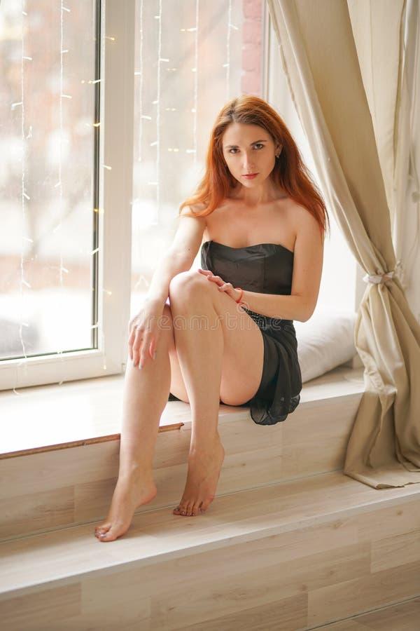 Powabny młodej dziewczyny obsiadanie w krótkiej sukni z bosym na białym windowsill z zasłonami zdjęcia stock